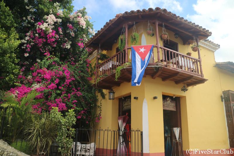 世界遺産の旧市街/キューバの大きな国旗が掲げられた店