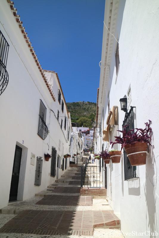 白い壁と飾りの花が並ぶ美しい町並み