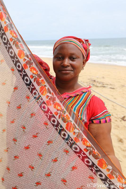 ビーチで布を売る女性