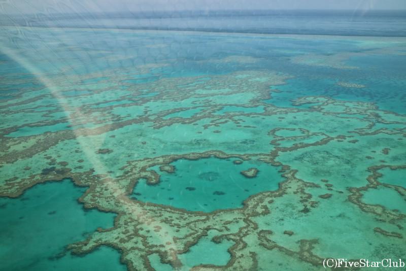 上空からサンゴ礁の美しい海を見下ろす